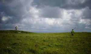 Dr. Catherine Frieman in a field in Cornwall with survey equipment