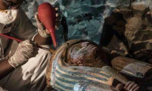 An Egyptian archaeologist restoring a wooden sarcophagus