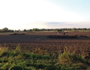 Archaeologists excavate in plowed fields near the village of Little Carlton in Lincolnshire, England. This rural region was once the site of a thriving settlement in the Middle Anglo-Saxon period (A.D. 710-850). Metal detector hobbyist Graham Vickers discovered a silver writing stylus here in 2011, prompting a closer archaeological look at the area. Excavations turned up multiple signs of literate and domestic life, from more styluses to dress pins to a hearth used for smelting. Surveys of the region revealed that the fields surrounding the spot used to be marsh, and that this site was an island of dry ground at the time it was settled.