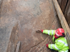 A MOLA archaeologist brushes off the exterior of the ice house.