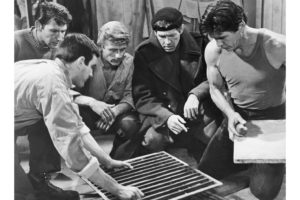 An unidentified actor removes a metal grate from the floor, while actors Lawrence Montaigne, John Leyton, James Coburn and Charles Bronson look on. From the film, 'The Great Escape,' directed by John Sturges, 1963.