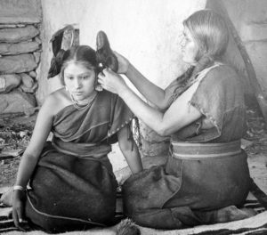 Hopi woman dressing hair of unmarried girl, c. 1900.