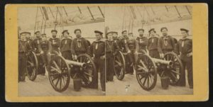Photograph shows a group portrait of seamen gathered around a mounted gun. The young boy seated on the gun is possibly the powder monkey.