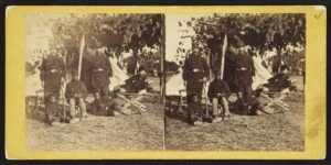 Stereograph showing Capt. B.S. Brown (left); Lt. John P. Shaw, Co. F 2nd Regt. Rhode Island Volunteer Infantry (center); and Lt. Fry (right) with African American men and boy at Camp Brightwood, D.C