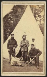 Three soldiers and two African American children, probably servants, posing in front of a tent.