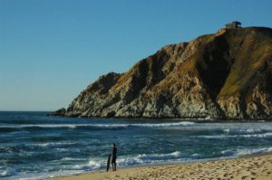Surfer standing on the beach with Devil's Slide bunker in the top right – Author: Wonderlane