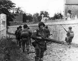 American paratroopers advance cautiously through a French cemetery after making successful landings at Utah Beach.