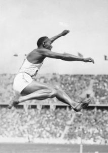 Jesse Owens with his record-setting long jump, wearing Dasslers' shoes, at the 1936 Berlin Olympics.