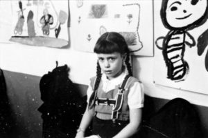 Young girl, half-length portrait, standing against wall displaying art work, in classroom in Chicago, Illinois. Photography by S. Kubrick.
