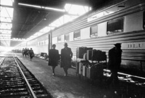 A man and a woman walking with a porter on the platform next to a railroad passenger car at a train station