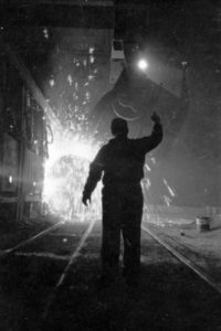 Steel worker in mill as molten steel spills from vat, in Chicago, Illinois, 1949. Image from Look photographic assignment 'Chicago City of Contrasts' by S. Kubrick.