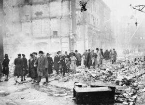 Office workers make their way to work through debris after a heavy air raid