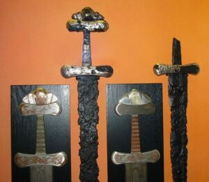 Two sword hilts on exhibit in Hedeby Museum. The sword on the left is from a Viking Age burial at Busdorf, Schleswig-Flensburg; Petersen type S, with silver and copper inlay work.