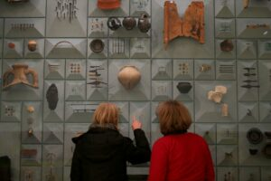 Visitors stand in front of Roman-era items at the London Mithraeum in London.