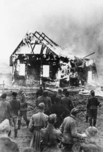 German soldiers and locals watch a Lithuanian synagogue burn, July 9, 1941.