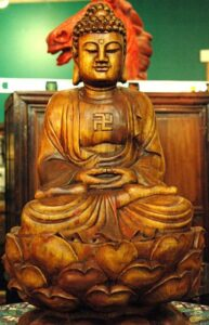 Wooden Buddha statue with gamadian (swastika).