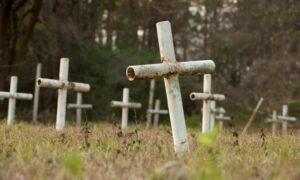 White metal crosses mark graves at the cemetery.