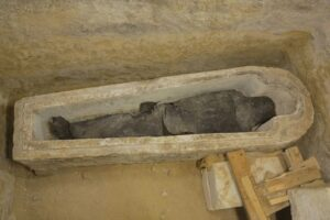 A priest named Ayput was interred in a stone sarcophagus carved in the shape of a human, a style known as anthropoid. The mummy's wrapping were coated with tar or resin, giving it a dark color.