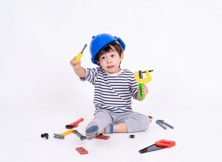 Little boy wearing blue helmet sitting and playing with construction equipment toy on white background
