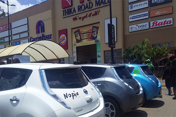 Electric vehicles in front of mall entrance