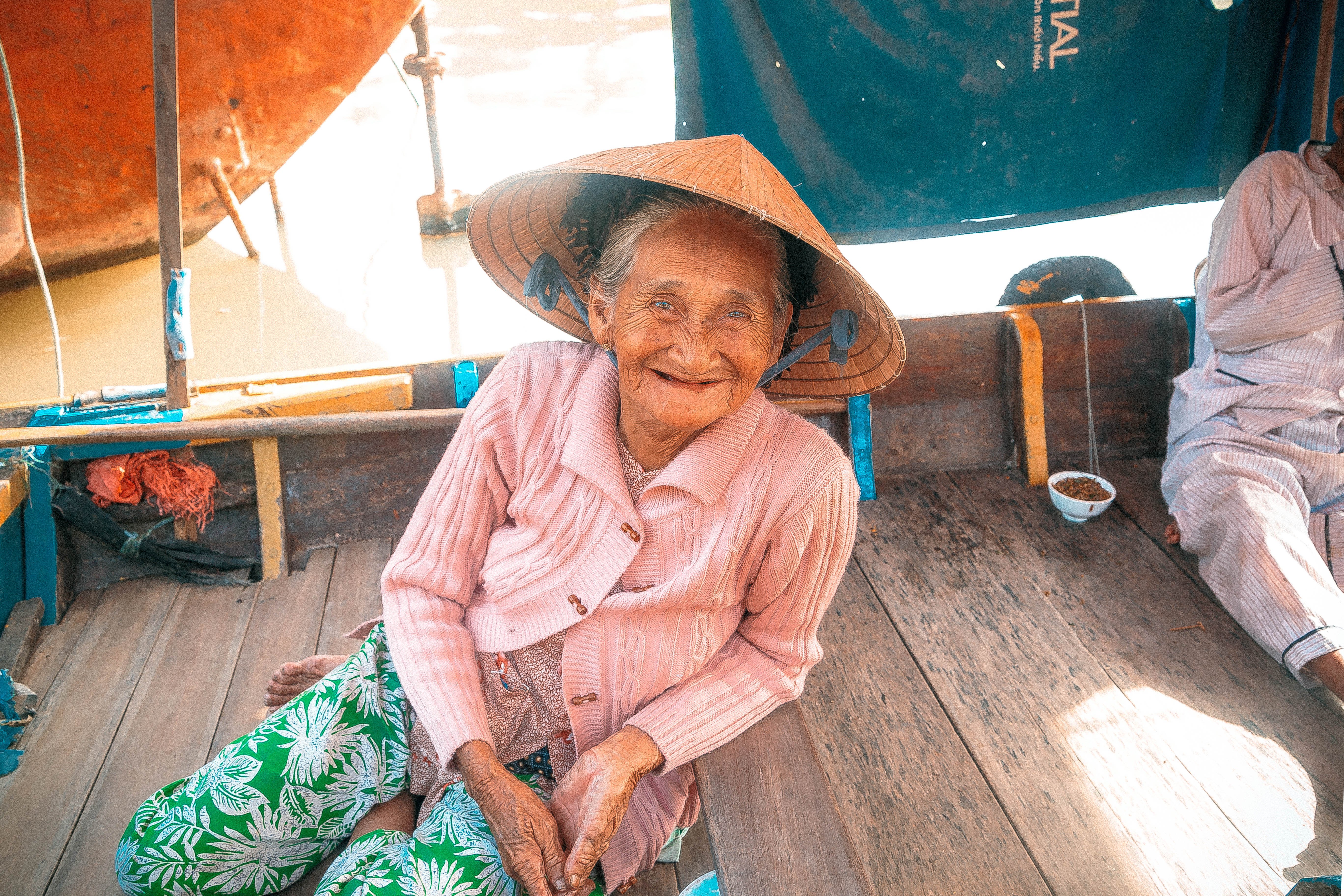 local vietnamese lady smiling in one of the boats next to the river in hoi an colourful vietnam