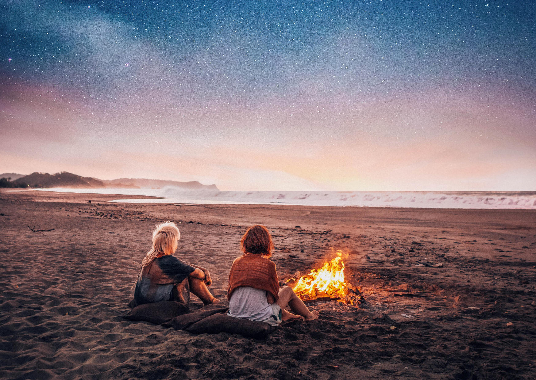 two girls sitting next to bonfire by the beach