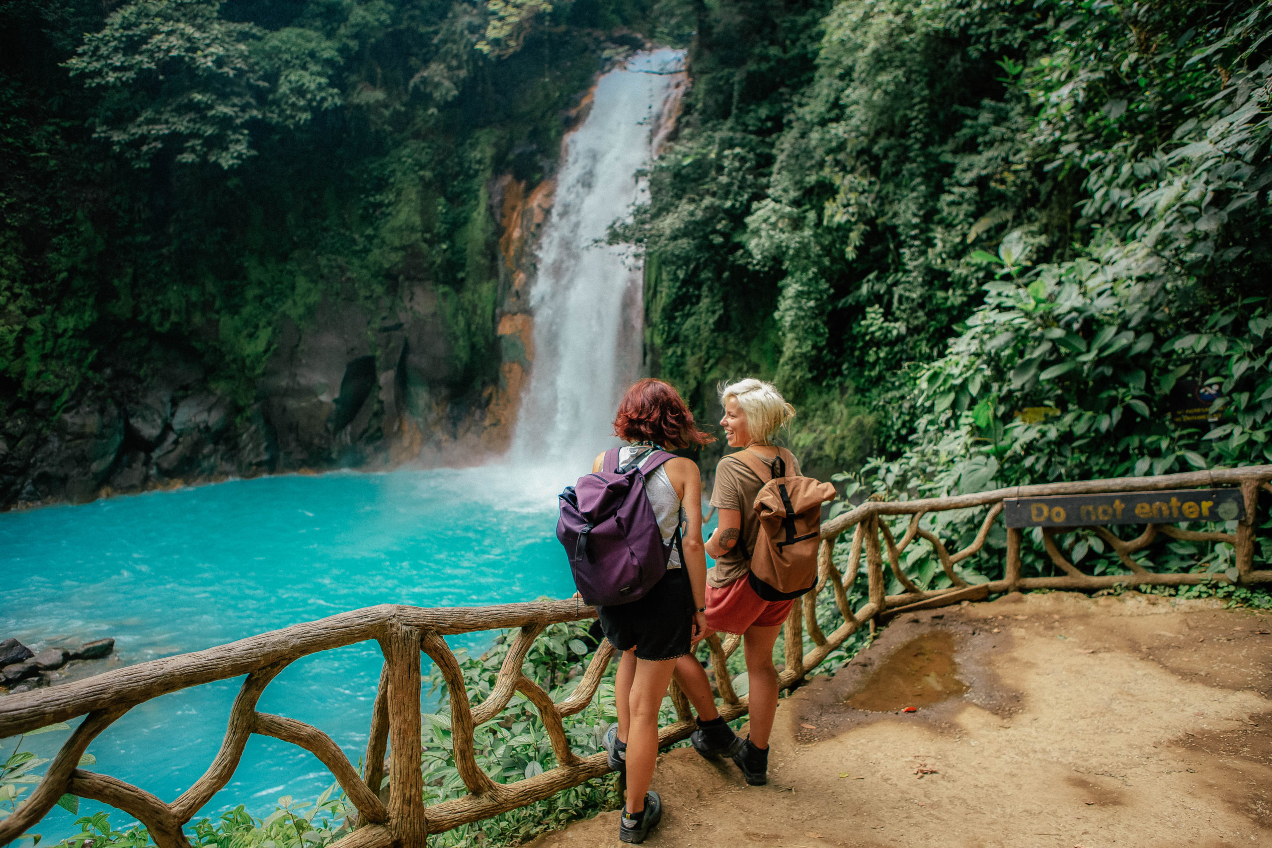 two girls standing in front of the waterfall in costa rica