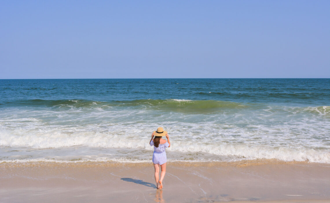 girl in striped romper with sunhat looking out at ocean