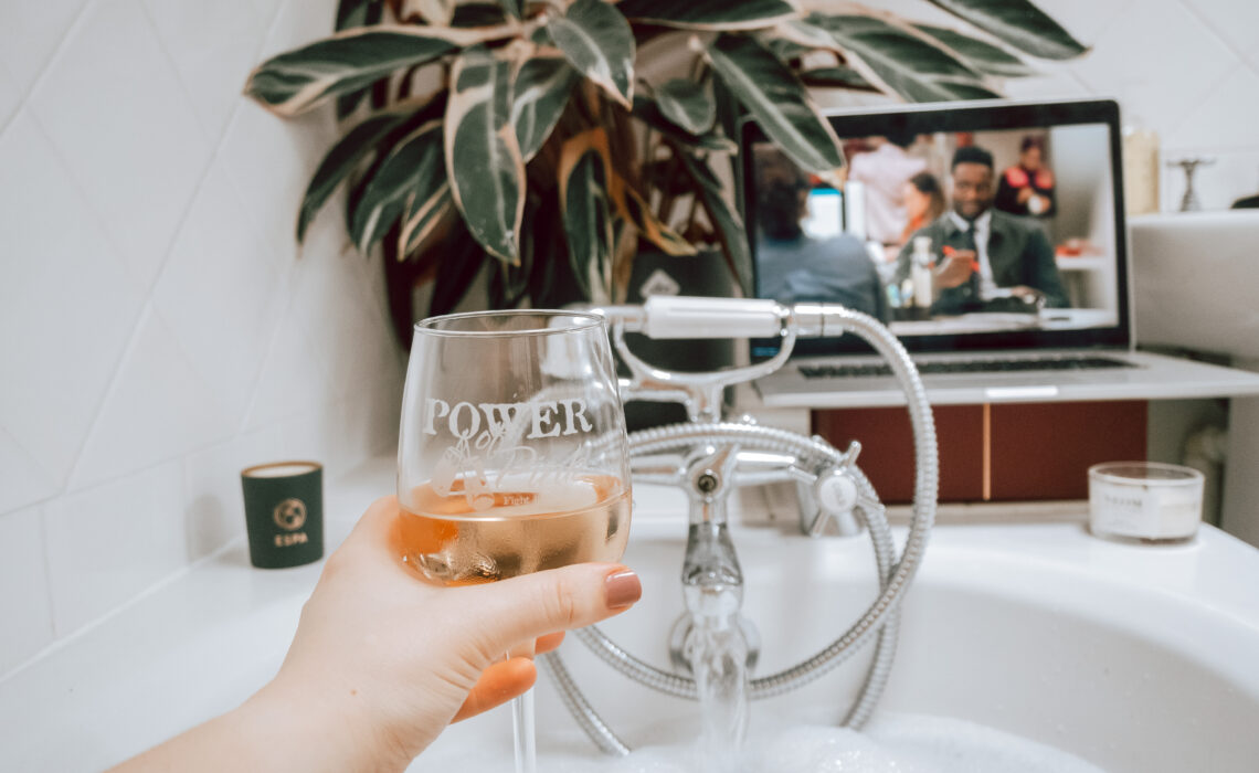 glass of rose in bath watching tv with plant in background