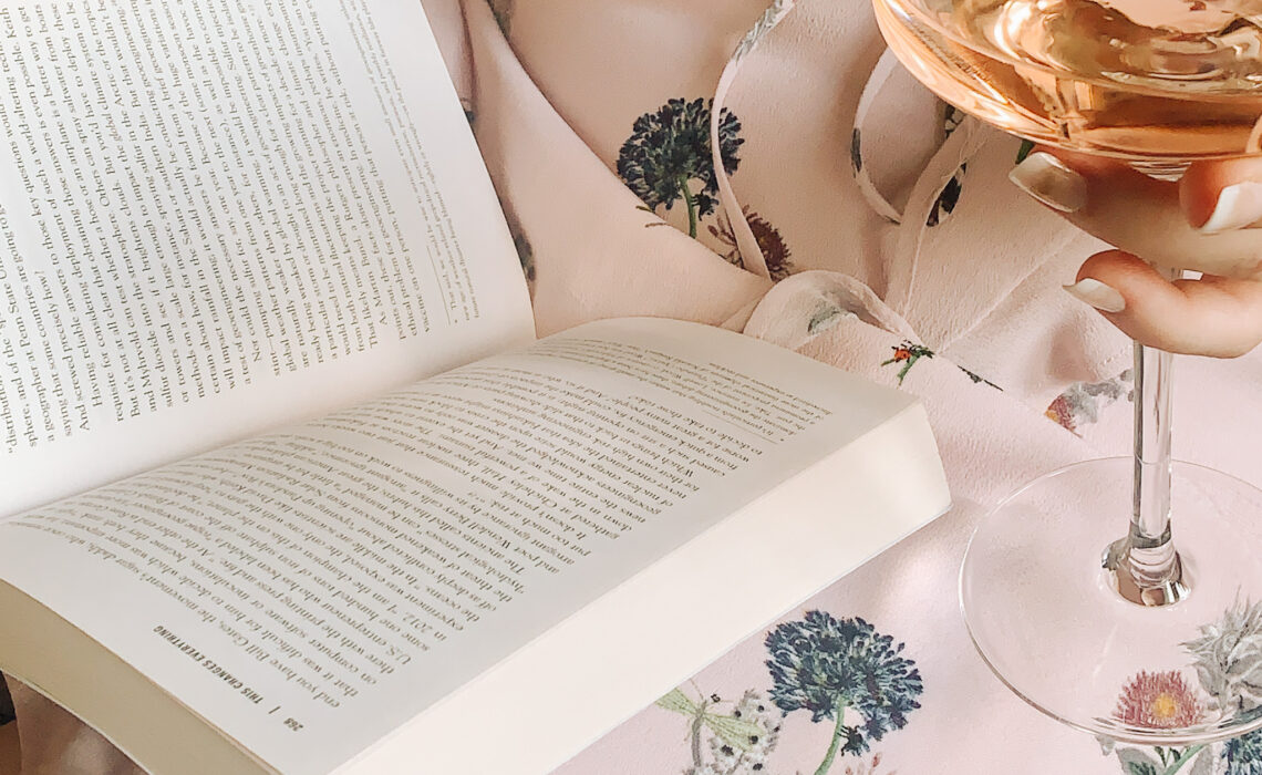 Book and rose wine against pale pink floral dress
