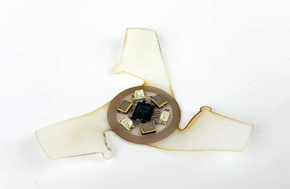 Top of larger microflier with coil antenna & sensors to detect ultraviolet rays.