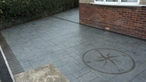 Platinum Grey Grand Ashlar Slate Printed Concrete Driveway with Charcoal Stained Borders and Etched Compass Feature