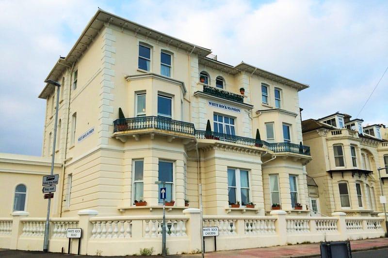 A victorian building set on a quiet hill