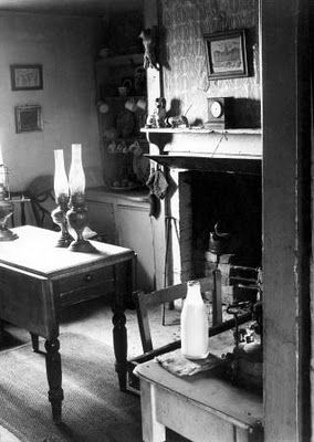 OIl lights in a 1950s rural interior showing fireplace and Victorian furniture.