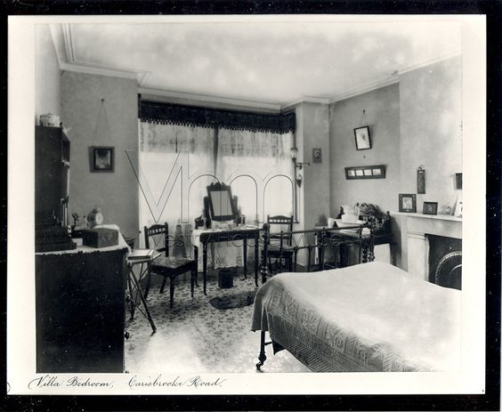 Victorian bedroom showing gas light lamp in the window. Linoleum flooring and fireplace is also shown.