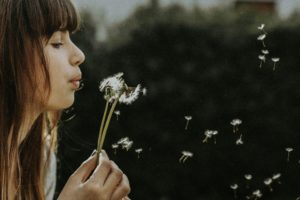Woman blowing flower to show power of breath