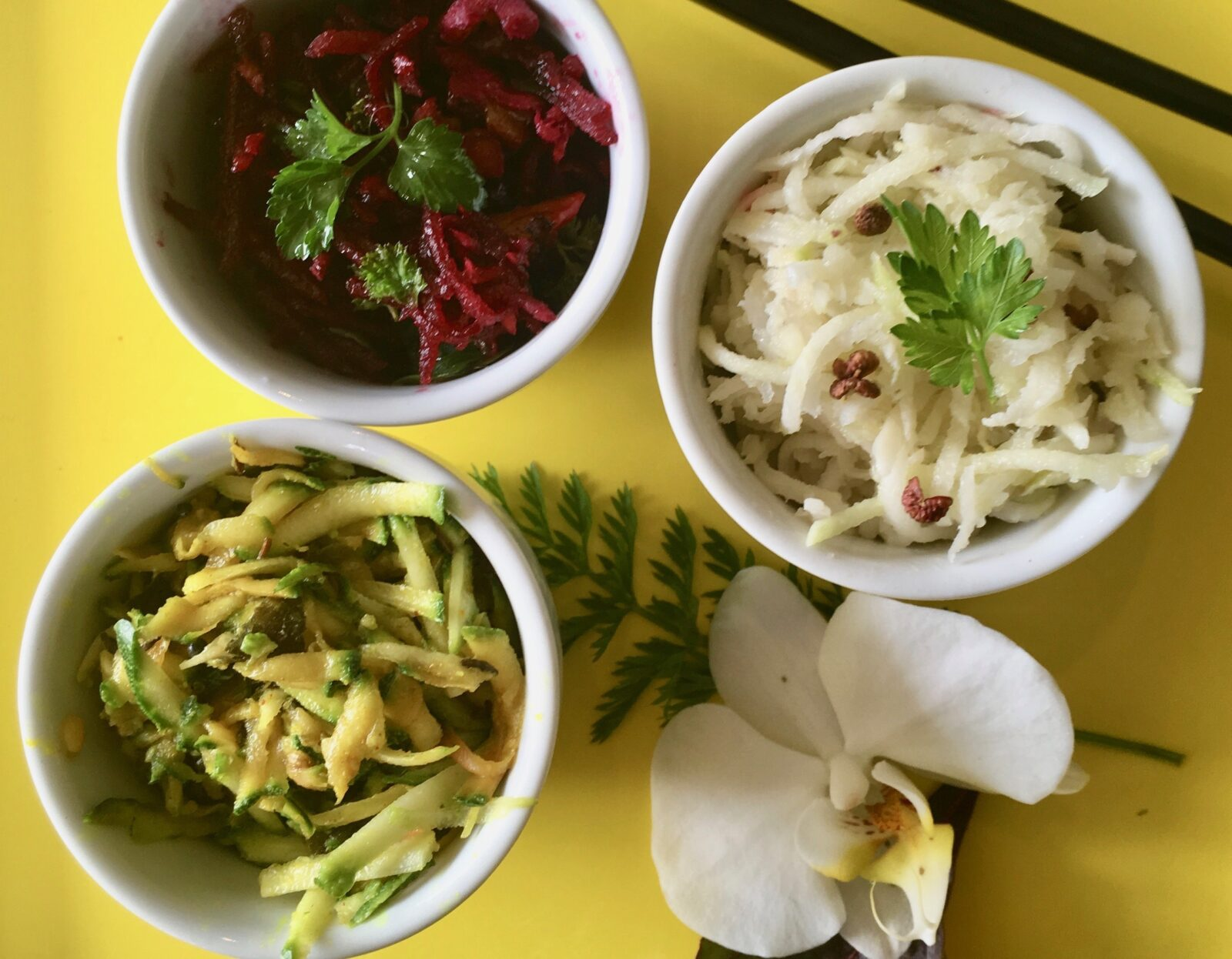 Three bowls of prepared vegetables.