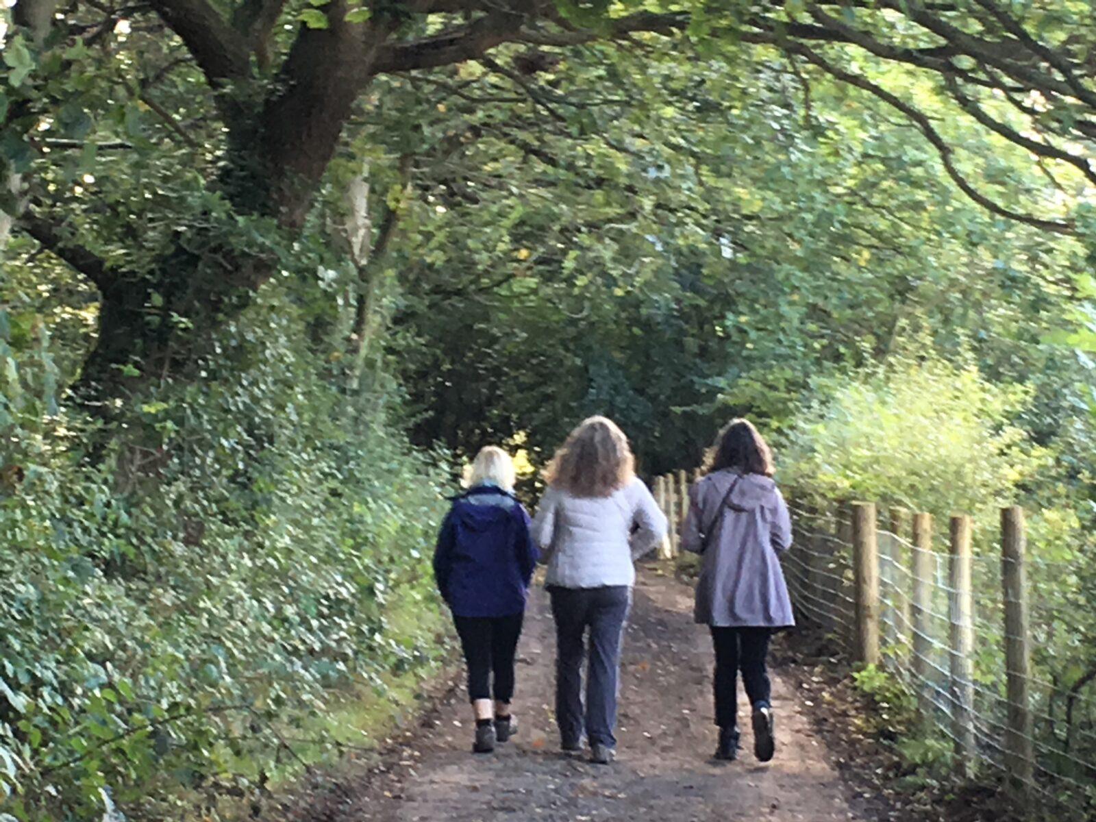 Three women walking in the lane beside Valley View.