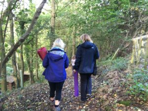 A group walking through the woodland to a yoga class.