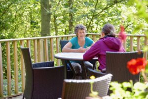 Lorraine talking to another woman on a deck in the woodland.