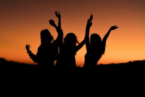 Three women silhouetted in the sunset.