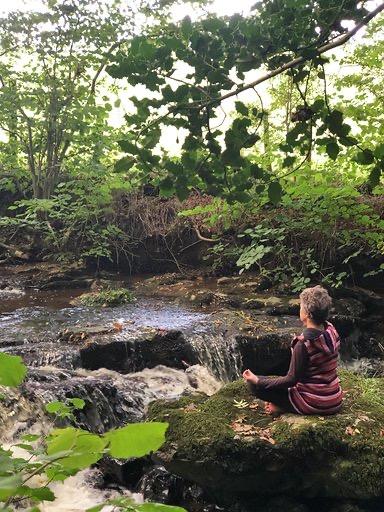 Lorraine meditating by a stream.