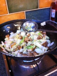 Cabbage being cooked in a wok with tofu.