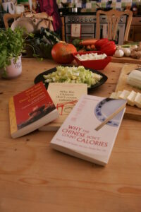 Three editions of Lorraine's book, 'Why the Chines Don't Count Calories', on a table with vegetables in the kitchen.
