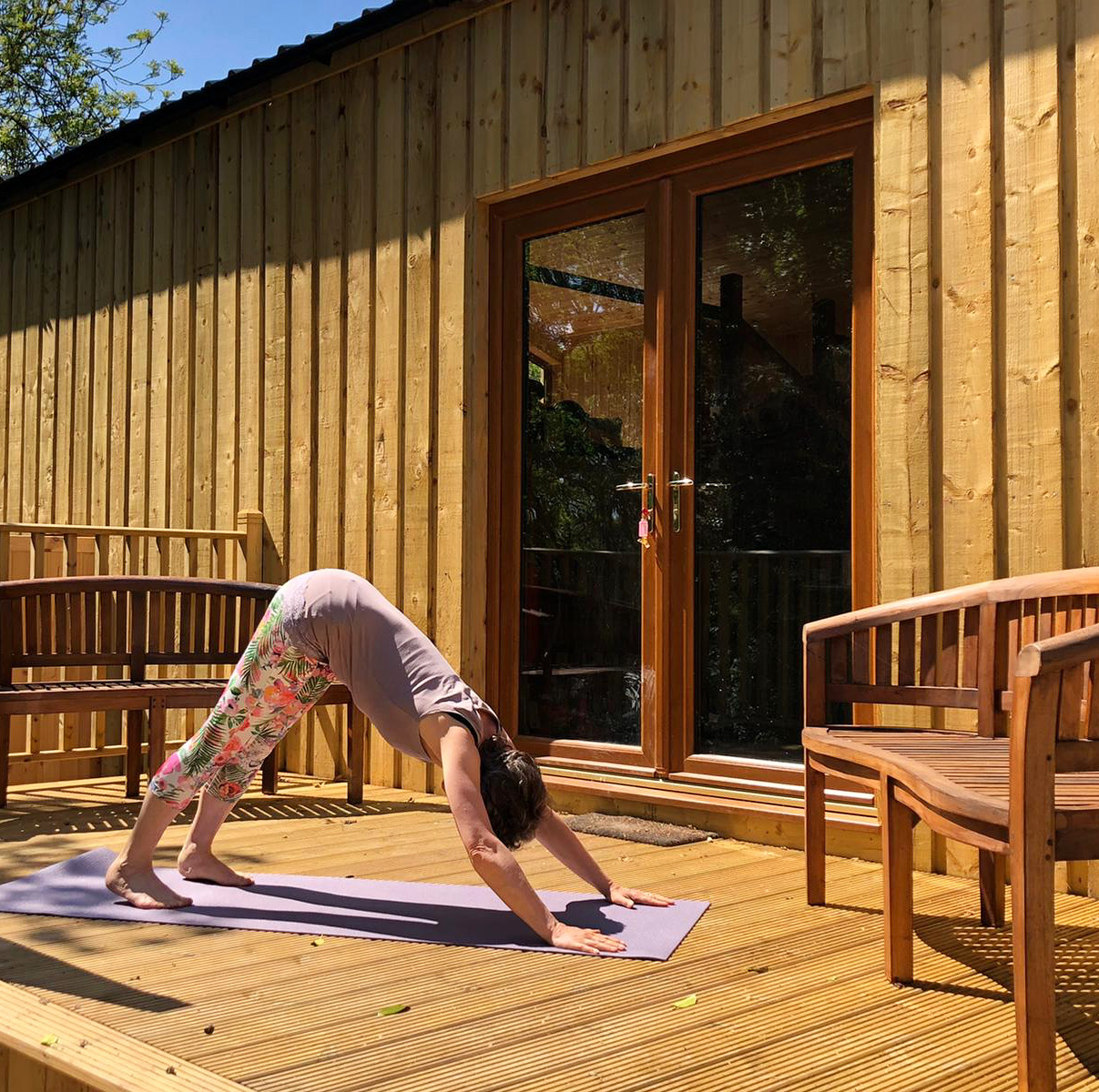 Lorraine doing yoga in the sun on the deck of the Yogandspice Studio.