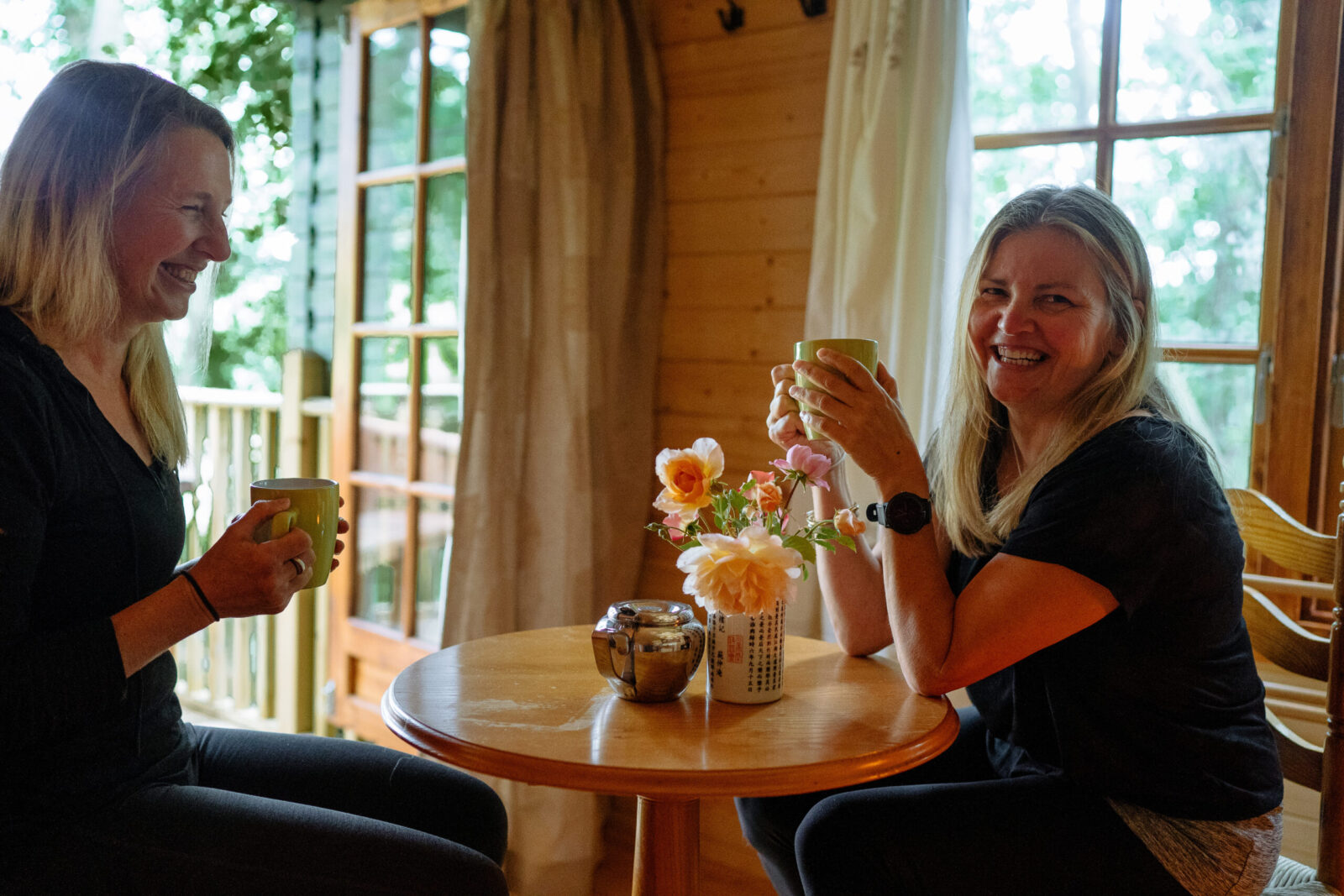 Two women laughing over coffee while on one of our yoga retreats in one of our cabins.
