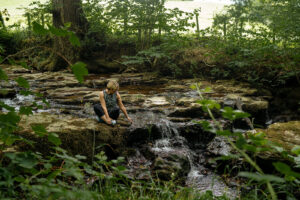 A woman sitting by the stream through the woodland at Valley View.