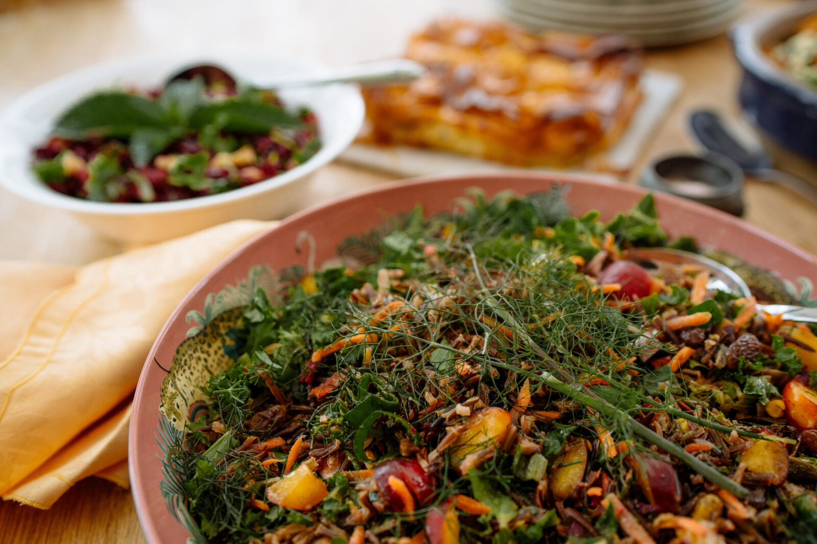 A serving bowl of salad prepared with herbs, fruits and seeds, served on one of our yoga retreats in North Yorkshire.
