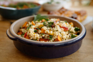 A serving bowl filled with a salad of giant couscous and sage.