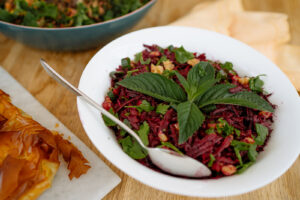 A bowl of beetroot with cumin and walnuts.
